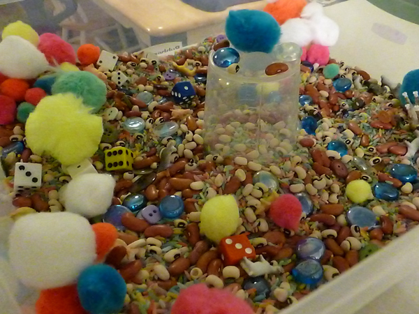Sensory bin with cotton balls, rice, beans and dice