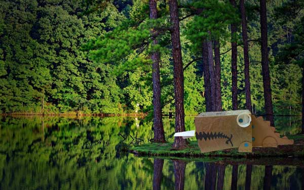 MAKEDO dinosaur out of recycled boxes, Photoshopped beside a lake