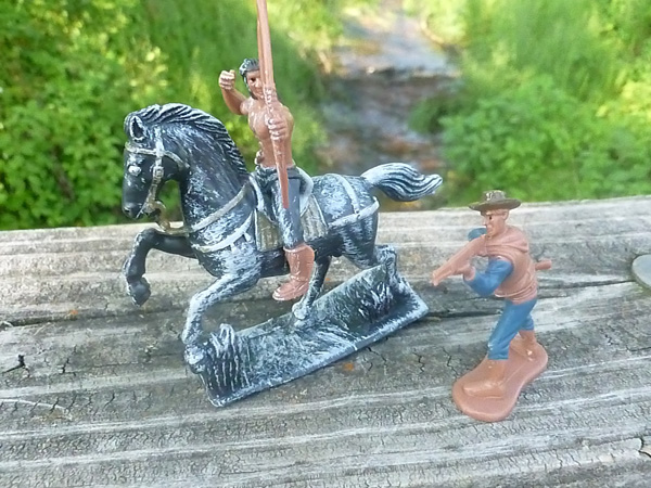 Cowboy and Indian toys posed outdoors