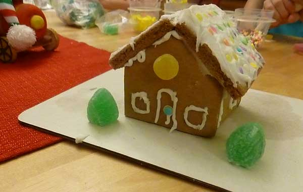 Yellow awning cottage gingerbread house from a kit