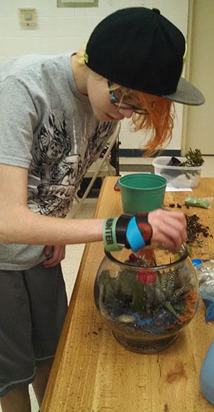 Sarah works on her desert terrarium at a Wildlife Watchers 4-H Club meeting.
