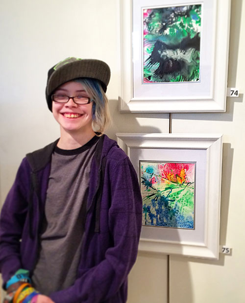 "This is Sarah with her art and mine at the York Art Association gallery. At the top is her painting ""The Dragon,"" and below is one of mine called ""Grapefruit Sunrise."""