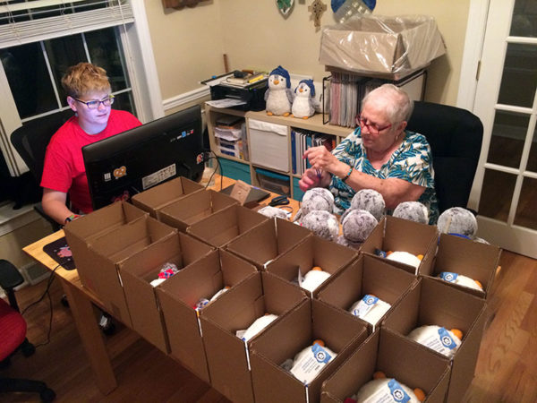 Unschooling in August 2017 on Unschool Rules: Shipping stuffed penguins by the dozens requires something of an assembly line. Here, I'm handling shipping labels and updating our online map; Mom is putting their little gift tags around their fat little necks with ribbon. Dan assembled the boxes and was taping them shut.