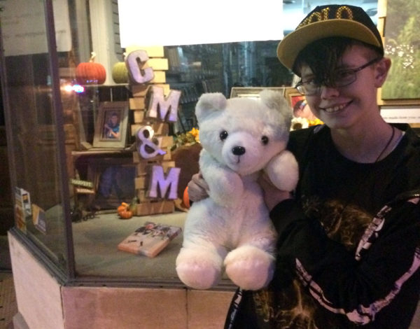 Unschooling in November 2017 on Unschool Rules: Ashar, her new stuffed bear Rivers, and our friend Nina's photography on display in a downtown storefront.